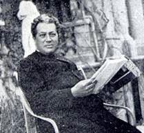 Félix Granda, leyendo en el jardín del Hotel de las Rosas, junto a la fuente de Goya y ante el edificio de las columnas. Hacia 1925.