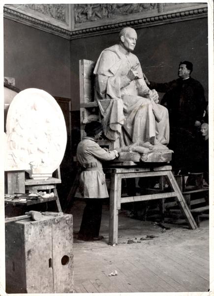 Don Félix Granda en sus Talleres de Arte, junto a la escultura de San Pío X realizada para Riese (Italia). En primer término, Julio Vicent, autor de la escultura y maestro en Talleres de esta disciplina.
